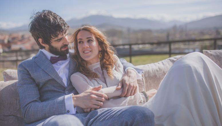 Novios en boda exterior abrazados en sillón